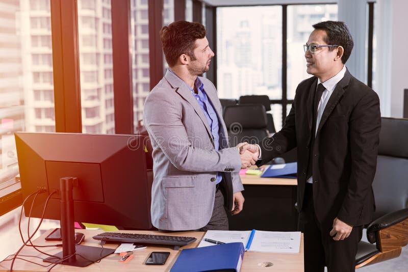 Corsa della miscela dell'uomo d'affari incontrare sorridere e stringere insieme le mani nell'ufficio fotografia stock
