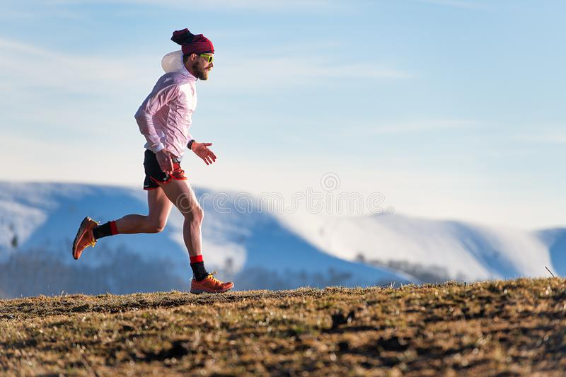 Corsa della montagna Formazione di un atleta fra i prati e la neve fotografia stock