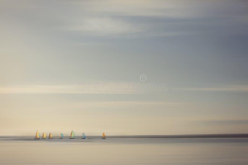 Corsa di barche a vela con le vele colourful, backgro immagini stock libere da diritti