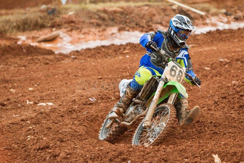 Corsa di motocross di Rider Negotiates Turn At Muddy fotografie stock libere da diritti