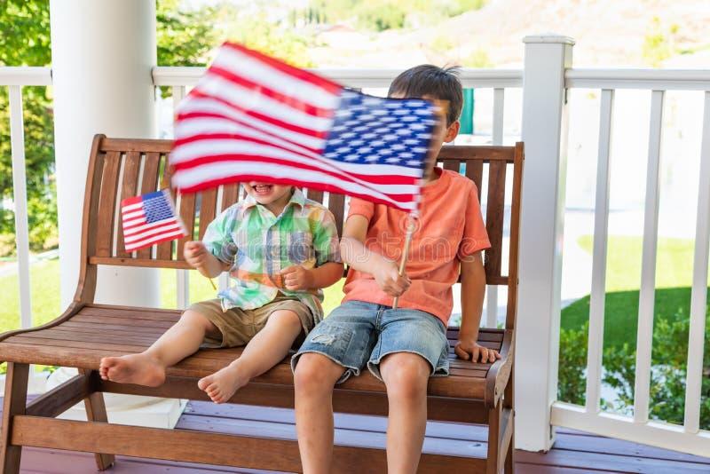 Corsa mista felice cinese e fratelli caucasici che giocano con le bandiere americane fotografie stock