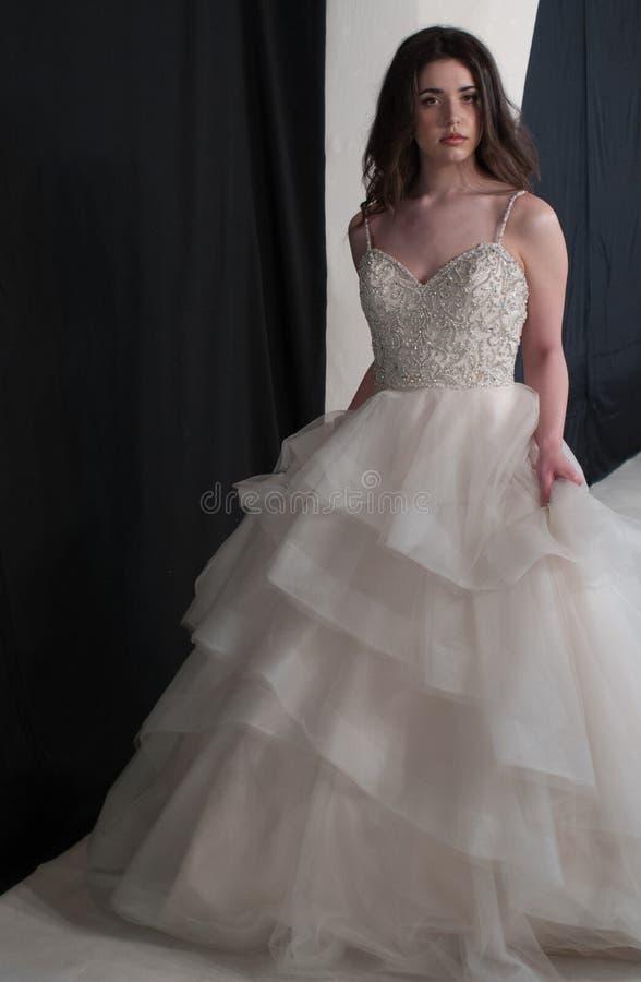 Corsage en ivoire de port de dentelle de jeune mariée de robe de mariage de jeune jeune mariée décoré des perles, jupe de Tulle a photos libres de droits