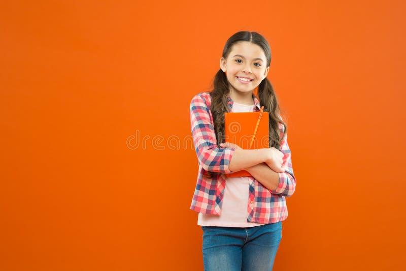 Corsi online per i bambini Fondo arancio del manuale dell'abbraccio del bambino della ragazza Lo studio ? divertimento Corso di s immagini stock