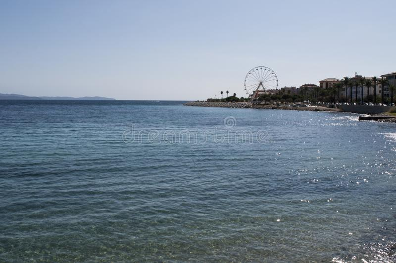 Ajaccio, beach, ferris wheel, Corsica, Corse du Sud, Southern Corsica, France, Europe. Corsica, 01/09/2017: crystal clear water of the Mediterranean Sea at the royalty free stock photos