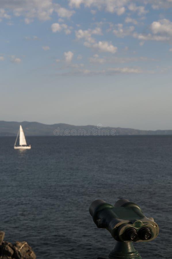 Corsica, Gulf of Ajaccio, Mediterranean Sea, sailboat, binoculars, relax. Corsica, 01/09/2017: binoculars pointed on a sailboat in the Mediterranean Sea in the royalty free stock photo