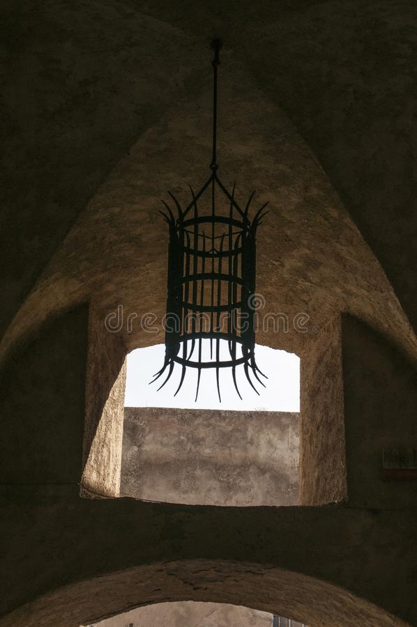 Calvi, Citadel, ancient walls, chandelier, skyline, Corsica, Corse, France, Europe, island. Corsica, 03/09/2017: an iron chandelier hanging in the ancient walls stock image