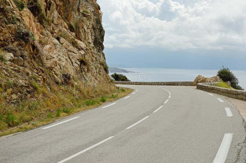 Corsican coastal road. The asphalt road is meandering along the steep cliff under the sea stock photography