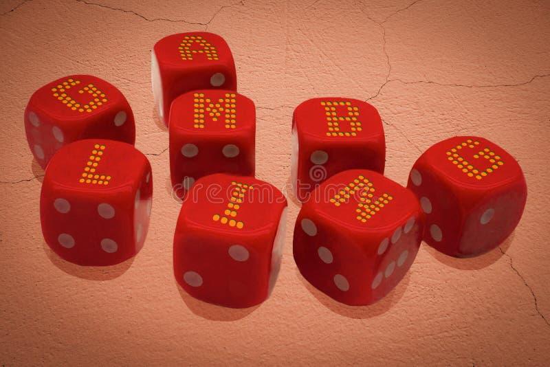 Corta en cuadritos con la inscripción QUE JUEGA El grupo de cubos del casino está en superficie de tierra agrietada abandonada Ca foto de archivo