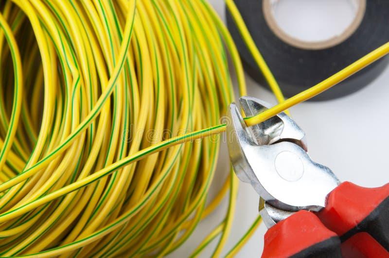 Cortaalambres, con un paquete de alambres de color verde amarillo y de cinta eléctrica foto de archivo libre de regalías