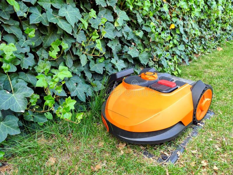 Cortac?sped anaranjado gen?rico del robot para la hierba de siega autom?tica en la estaci?n de acoplamiento fotos de archivo