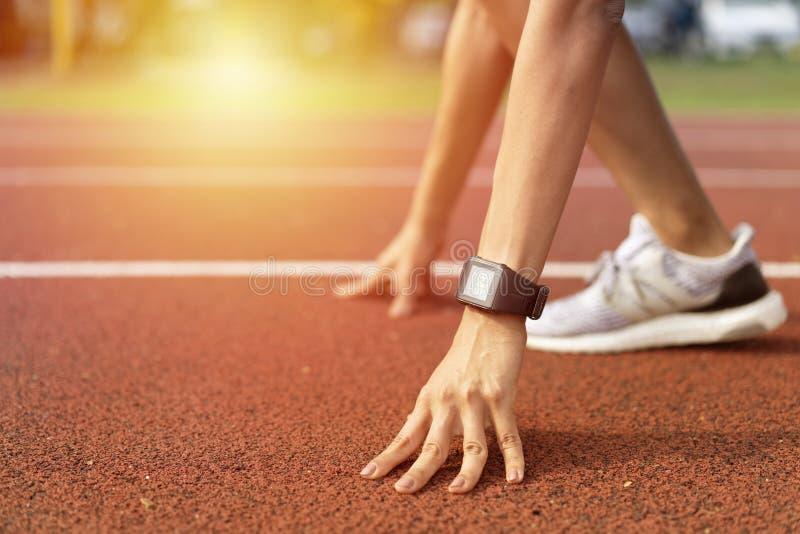 Cortado baixo ângulo de atleta feminina no ponto de partida de uma pista de corrida com luz do dia, preparando-se para um fotos de stock
