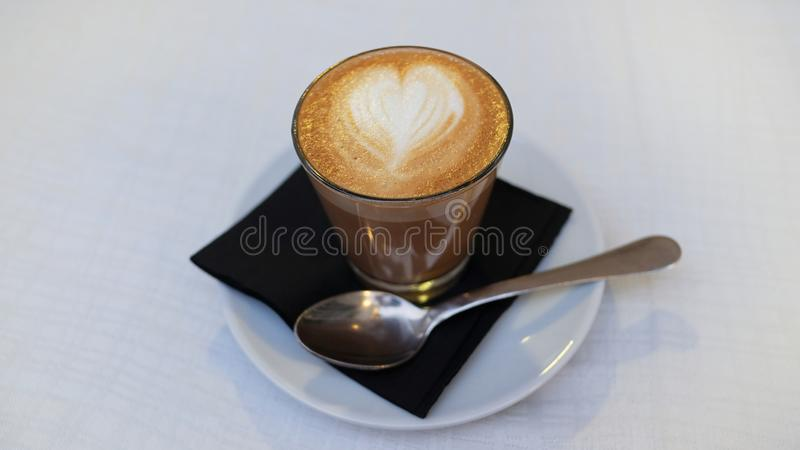 Cortado de café, un café espagnol traditionnel servi en verre transparent avec un art en forme de coeur de latte de mousse sur le photographie stock