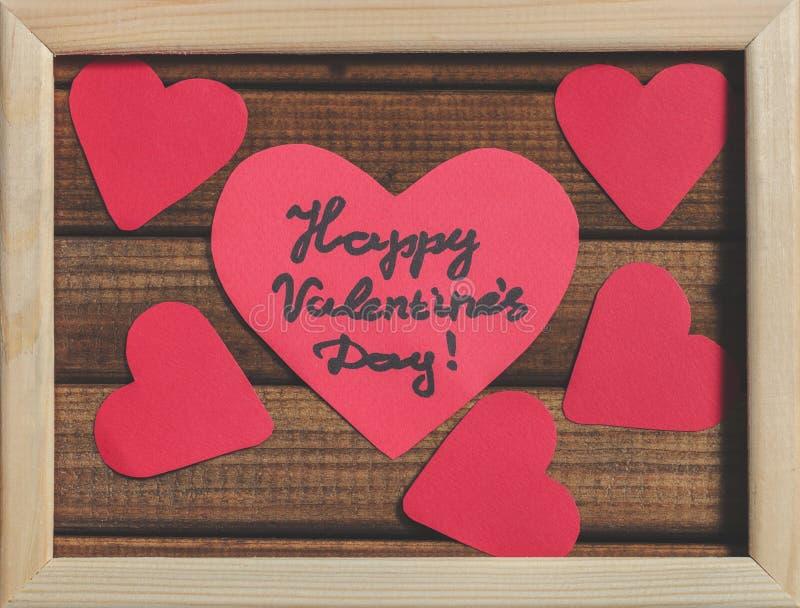 Cortado de corações de papel vermelhos no fundo de madeira no quadro de madeira, dia feliz do ` s do Valentim dos cumprimentos imagem de stock