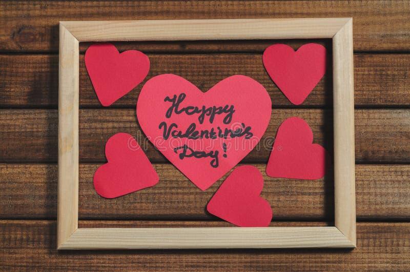 Cortado de corações de papel vermelhos no fundo de madeira no quadro de madeira, dia feliz do ` s do Valentim dos cumprimentos imagem de stock royalty free