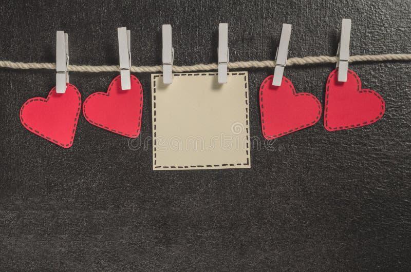 Cortado de corações de papel vermelhos pendure na corda no primako pequeno, dia feliz do ` s do Valentim dos cumprimentos imagem de stock royalty free