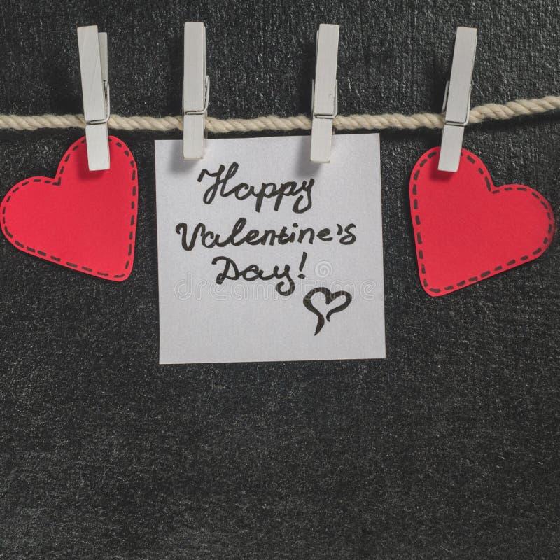 Cortado de corações de papel vermelhos pendure na corda no primako pequeno, dia feliz do ` s do Valentim dos cumprimentos fotos de stock royalty free