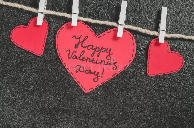 Cortado de corações de papel vermelhos pendure na corda no primako pequeno, dia feliz do ` s do Valentim dos cumprimentos imagens de stock