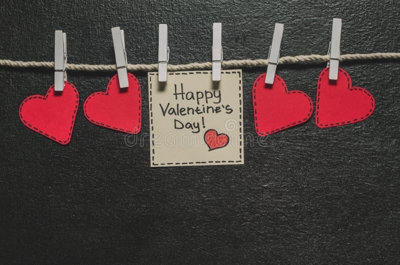 Cortado de corações de papel vermelhos pendure na corda no primako pequeno, dia feliz do ` s do Valentim dos cumprimentos foto de stock