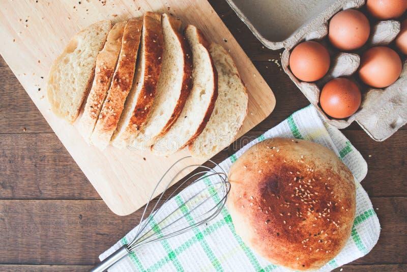 Cortado e naco do pão caseiro com os ovos frescos no fundo de madeira, configuração do plano foto de stock