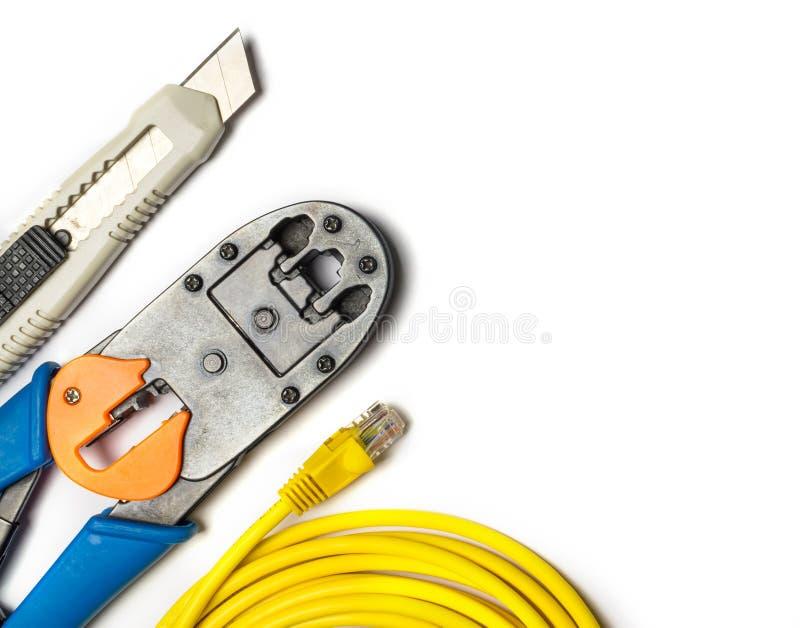 Cortador, arrugador, cordón de remiendo amarillo y conectores fotos de archivo libres de regalías
