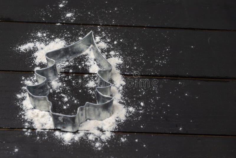 Cortador da cookie da árvore de Natal no fundo de madeira com farinha imagem de stock royalty free
