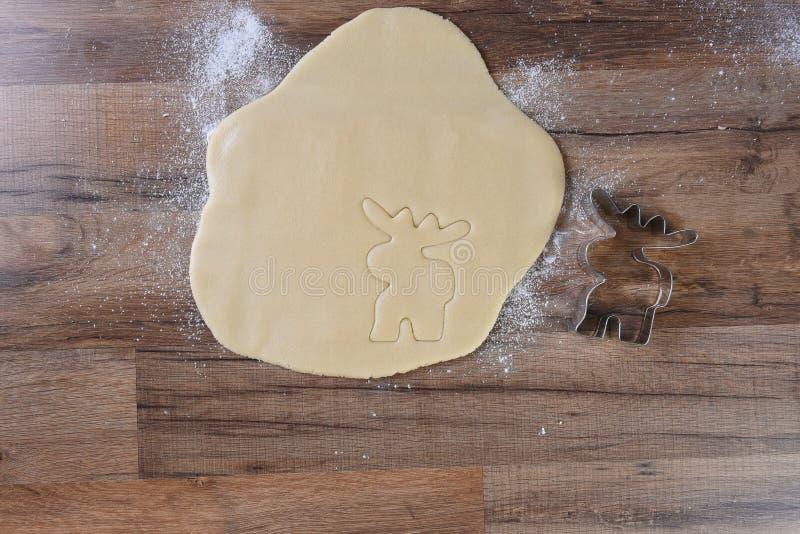 Cortador dado forma alces da cookie ao lado da massa desenrolada em uma mesa de cozinha de madeira fotografia de stock royalty free