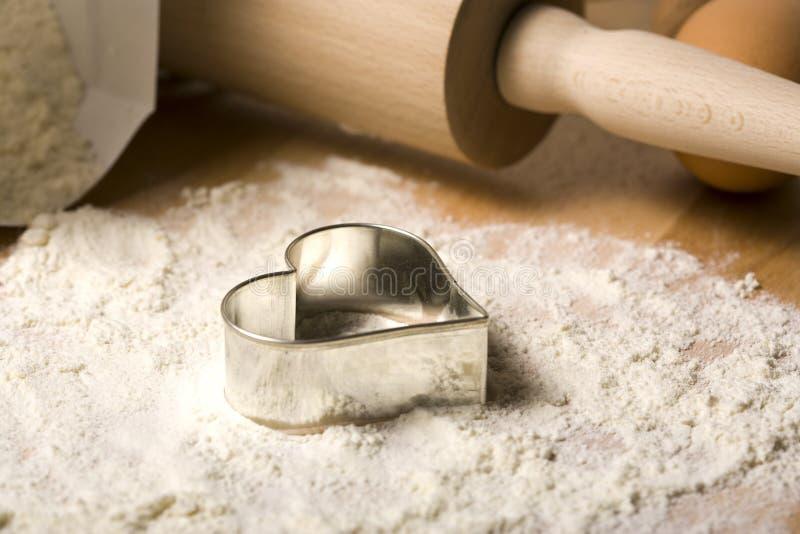 Cortador dado forma coração do bolinho na farinha foto de stock royalty free
