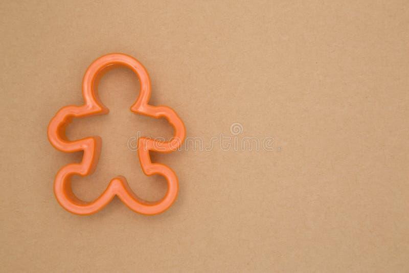 Cortador de la galleta del hombre de pan de jengibre en un fondo de Kraft foto de archivo libre de regalías