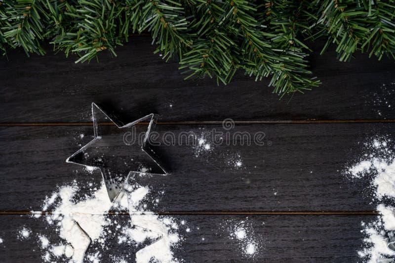 Cortador de la galleta de la estrella de la Navidad en el fondo de madera con la harina imagenes de archivo