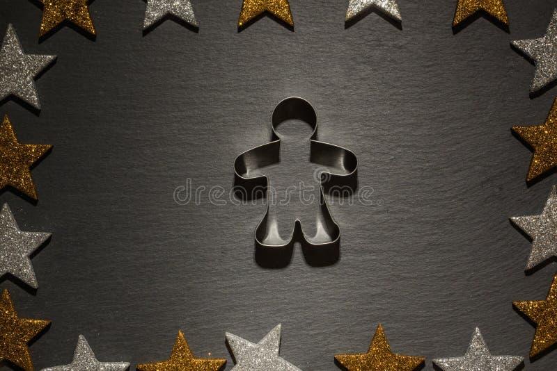 Cortador de la galleta para el hombre de pan de jengibre en fondo de la pizarra foto de archivo