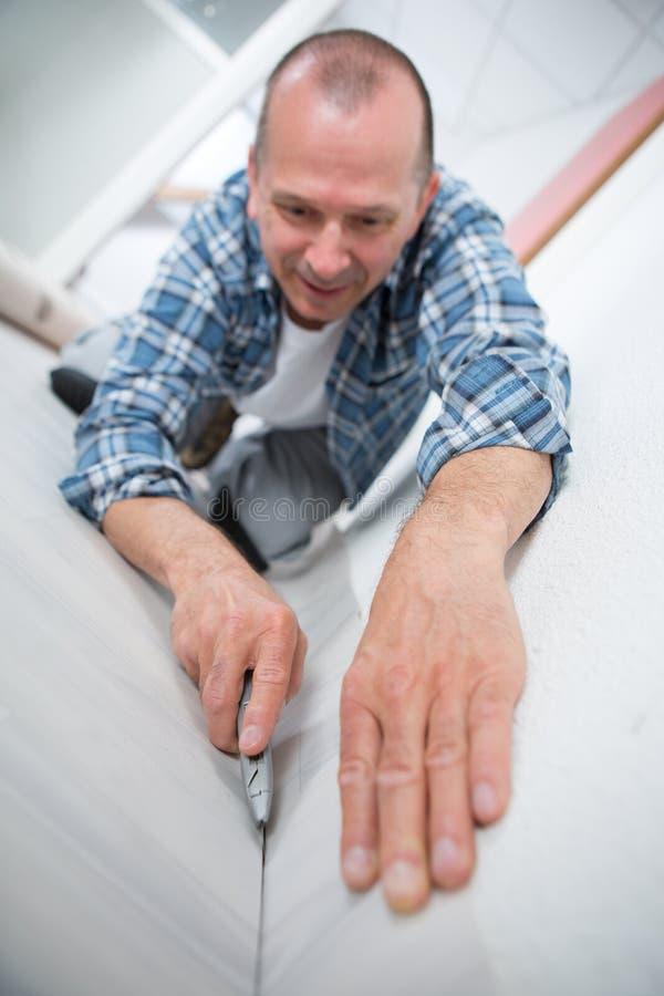 Cortador de sexo masculino de Installing Carpet With del ajustador de la alfombra foto de archivo