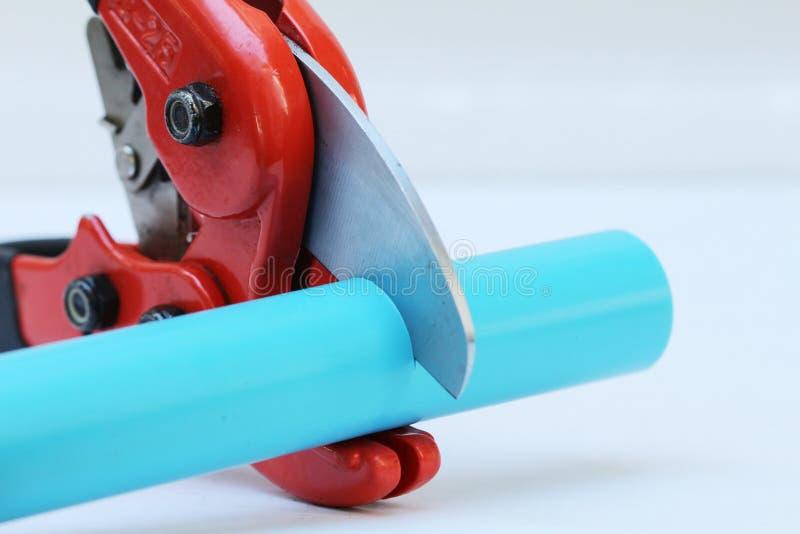 Cortador de tubo de agua del PVC con el cuerpo rojo del metal, la manija de goma negra y la cuchilla gruesa aguda en el fondo bla imagenes de archivo