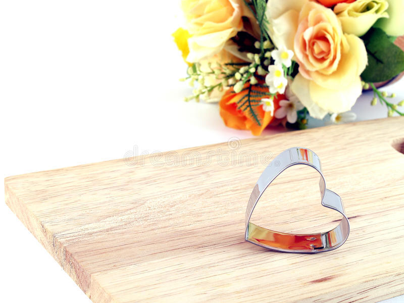 Cortador en forma de corazón de las galletas en tabla de cortar de madera con la flor colorida de la tela foto de archivo