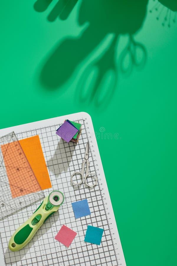 Cortador giratório, régua, partes quadradas brilhantes da tela, pilha das partes brilhantes do quadrado da tela, tesouras na este fotografia de stock