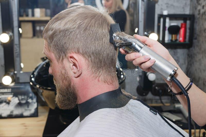 Cortadora del pelo del peluquero El amo proporciona un corte de pelo imagen de archivo libre de regalías
