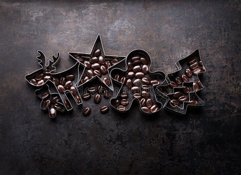 Cortadores das cookies do Natal - árvore de Natal, cervo, estrela, forma de mann do pão-de-espécie com feijões de cacau fotografia de stock