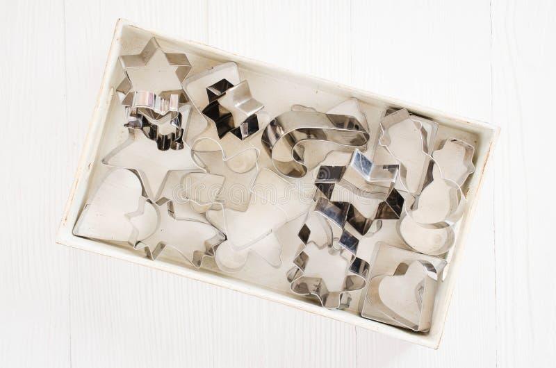 Cortadores de la galleta del metal, para la hornada de la Navidad en la tabla de madera blanca imagen de archivo libre de regalías