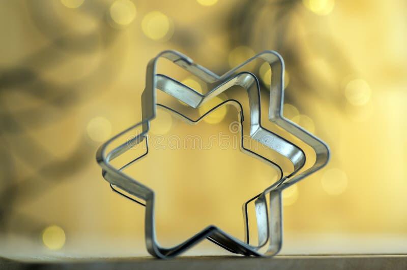 Cortadores metálicos das estrelas do Natal em luzes de Natal mágicas no fundo fotografia de stock royalty free