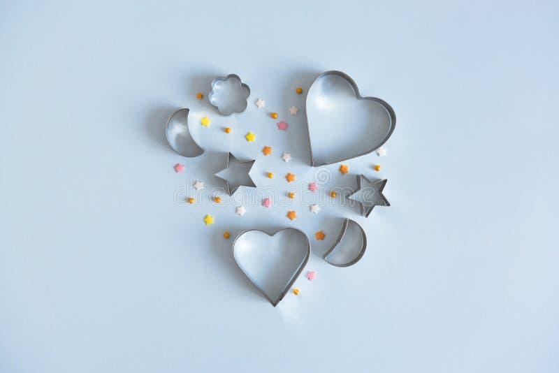 Cortadores metálicos de la galleta en forma del corazón en fondo azul Concepto de la panadería y del confitero Copie el espacio imagenes de archivo