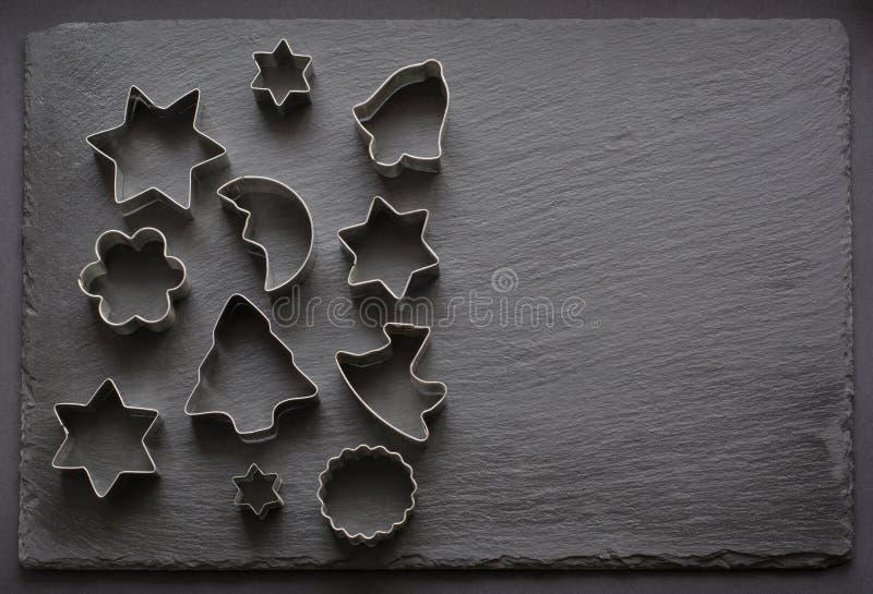 cortadores Navidad-temáticos de la galleta Cortadores de la galleta de la Navidad en fondo negro Tarjeta del día de fiesta fotografía de archivo