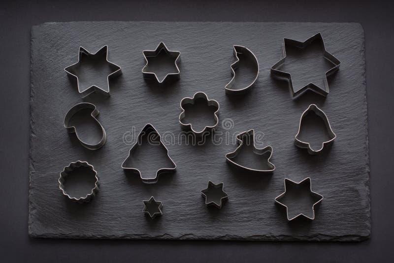 cortadores Navidad-temáticos de la galleta Cortadores de la galleta de la Navidad en negro Tarjeta del día de fiesta foto de archivo