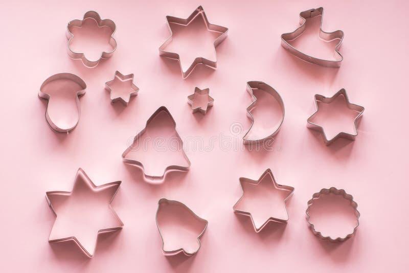 cortadores Navidad-temáticos de la galleta Cortadores de la galleta de la Navidad en rosa Tarjeta del día de fiesta foto de archivo libre de regalías