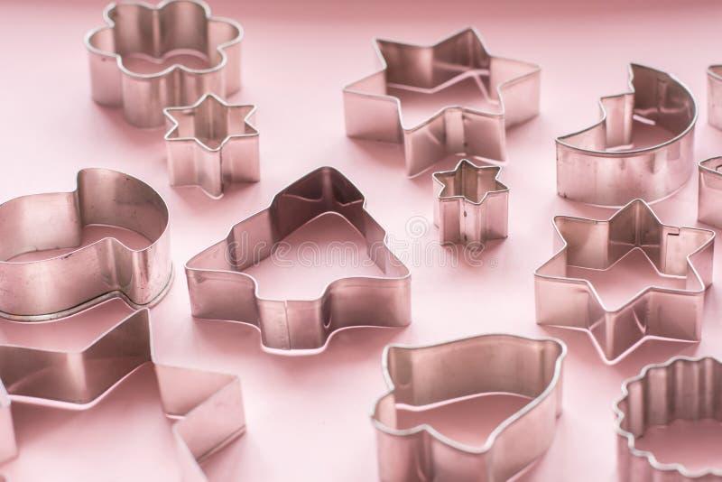 cortadores Navidad-temáticos de la galleta Cortadores de la galleta de la Navidad en rosa Tarjeta del día de fiesta fotos de archivo