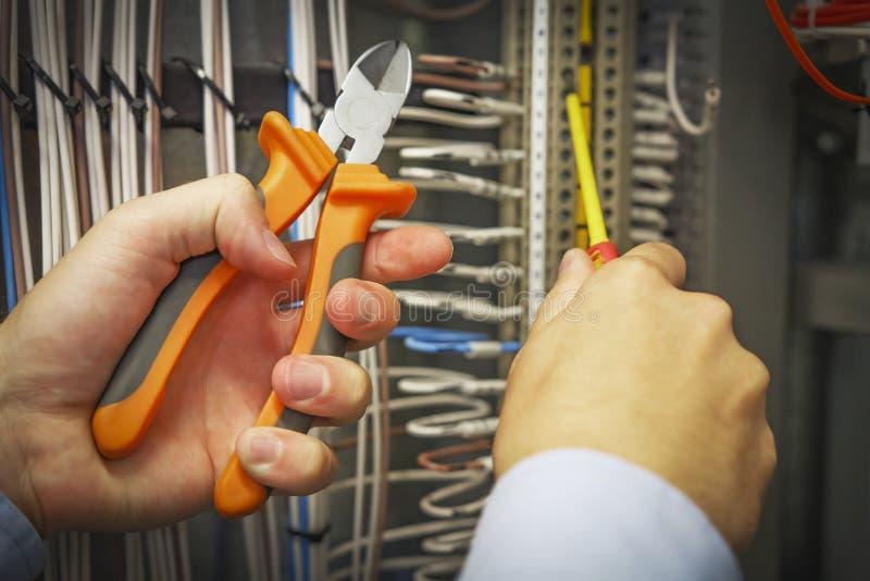 Cortadores y destornillador en manos del primer del electricista contra fondo del bloque de terminales eléctrico imagenes de archivo