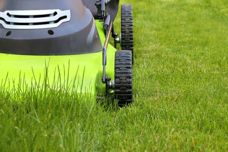 Cortando a grama com cortador de grama bonde imagens de stock royalty free