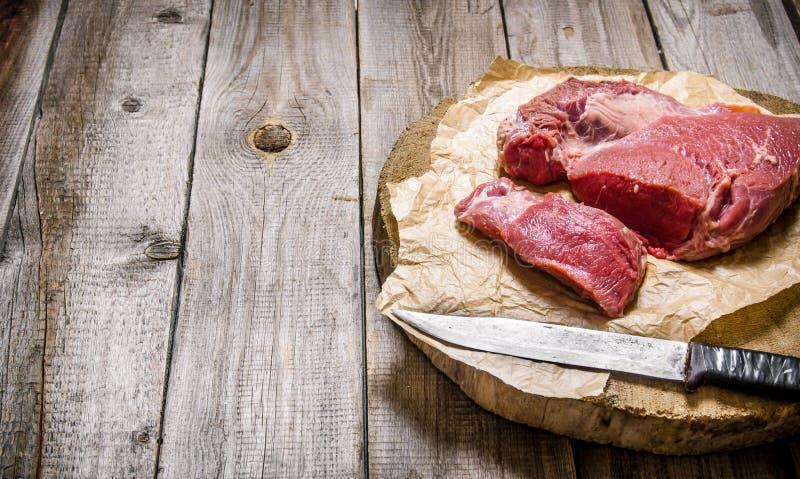 Cortando la carne cruda un cuchillo grande En el vector de madera foto de archivo libre de regalías