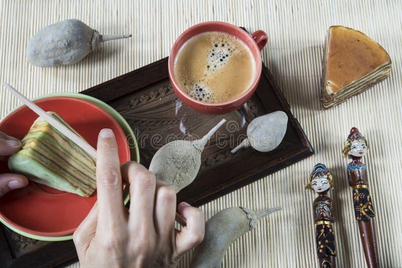 Cortando la torta de varias capas llamó legit o el spekkoek del lapislázuli, con la servilleta de bambú y el recuerdo indonesio imagen de archivo libre de regalías