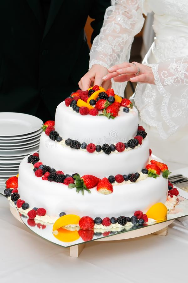 Cortando o bolo de frutas fresco do casamento imagens de stock royalty free