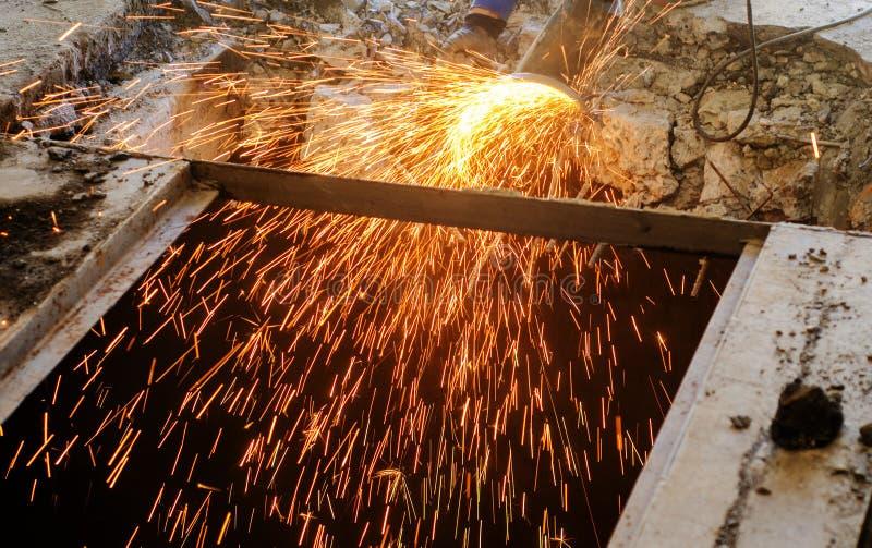 Cortando o reforço do metal no concreto reforçado Faíscas da fricção com metal Trabalho da desmontagem Serra elétrica circular imagem de stock royalty free
