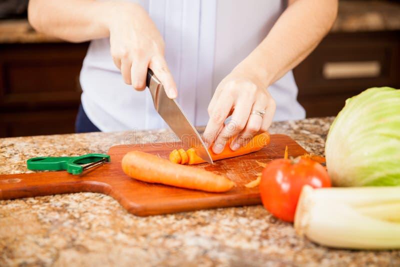 Cortar algunas zanahorias en la cocina foto de archivo libre de regalías